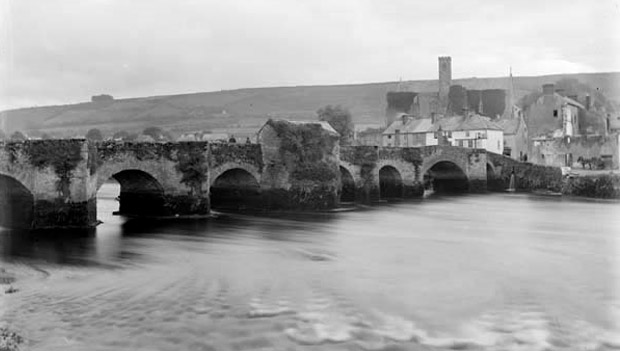 The original old bridge with covered centre piece which was completed in 1477. The parish church in Carrick-beg is in the background
